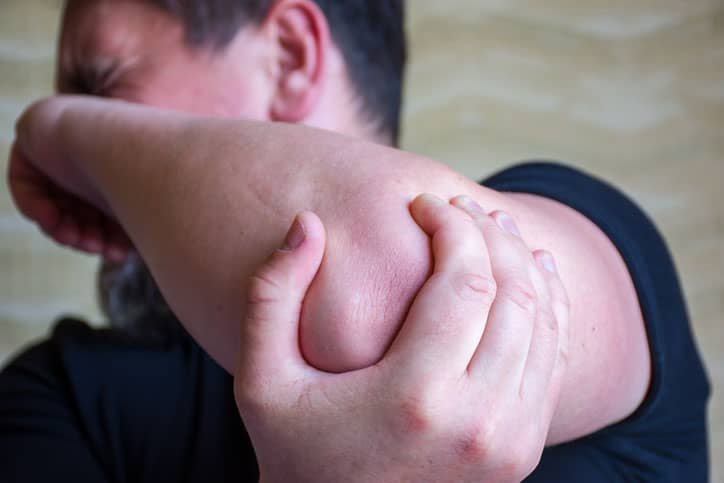 Man suffering from cubital tunnel syndrome holding his elbow in pain