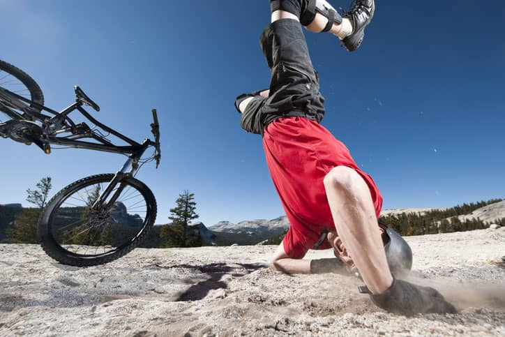 Mountain biker in red shirt flips on his head breaking his clavicle, which is the most common mountain bike injury.